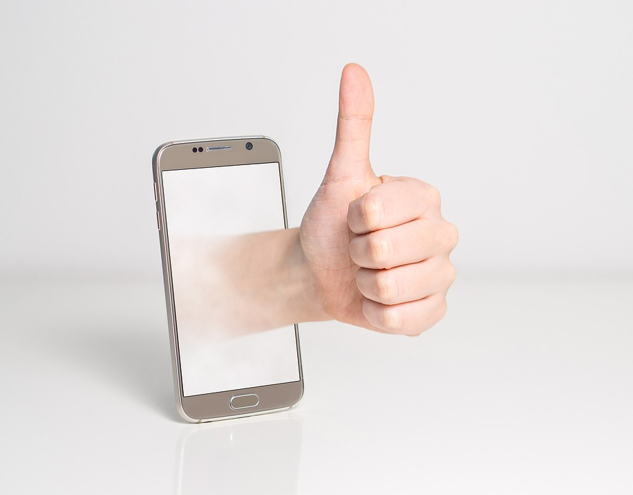 Thumb up, beside a cell phone