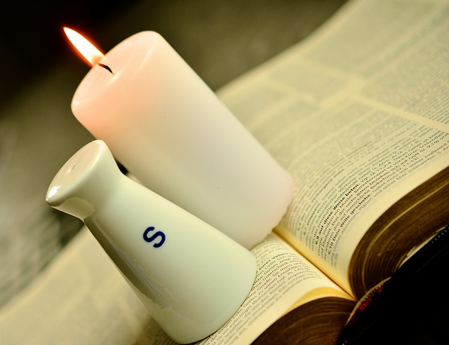 a bible with a salt shaker and and candle resting on it