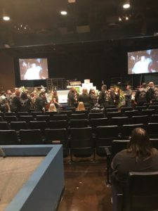 a large auditorium with lots of people walking around, most of them wearing motorcycle colors and a open casket in the backgroud