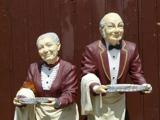two well dressed servants with sliver serving trays