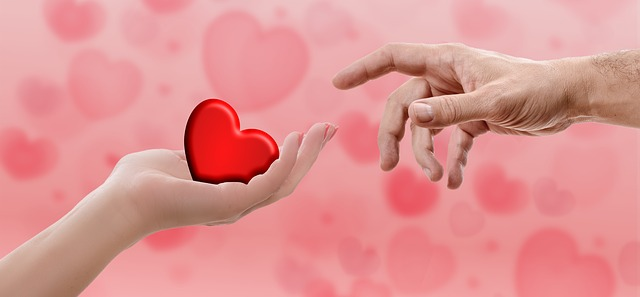 A red heart held in a hand, and being touched by someone's finger.