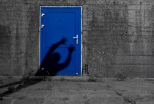 Grey brick wall and cement ground with a bright blue door in the middle of the wall.  A shadow of a person reaches for the handle on the door.