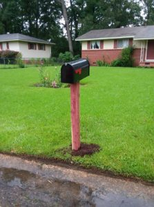 cedar post with black mailbox