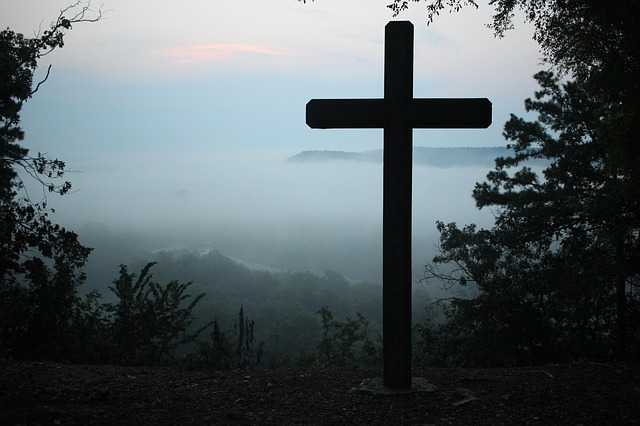 picture of a cross with a background of a peaceful sunset