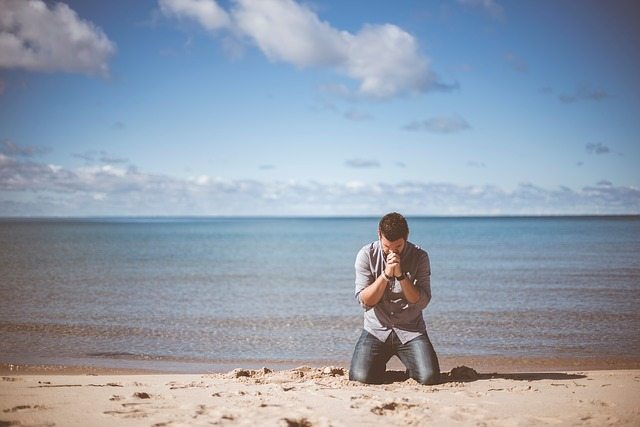 man kneeling, beach, sea